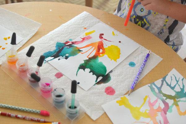 Kids use liquid watercolors and straws to move the paint around on the paper and make colorful art.