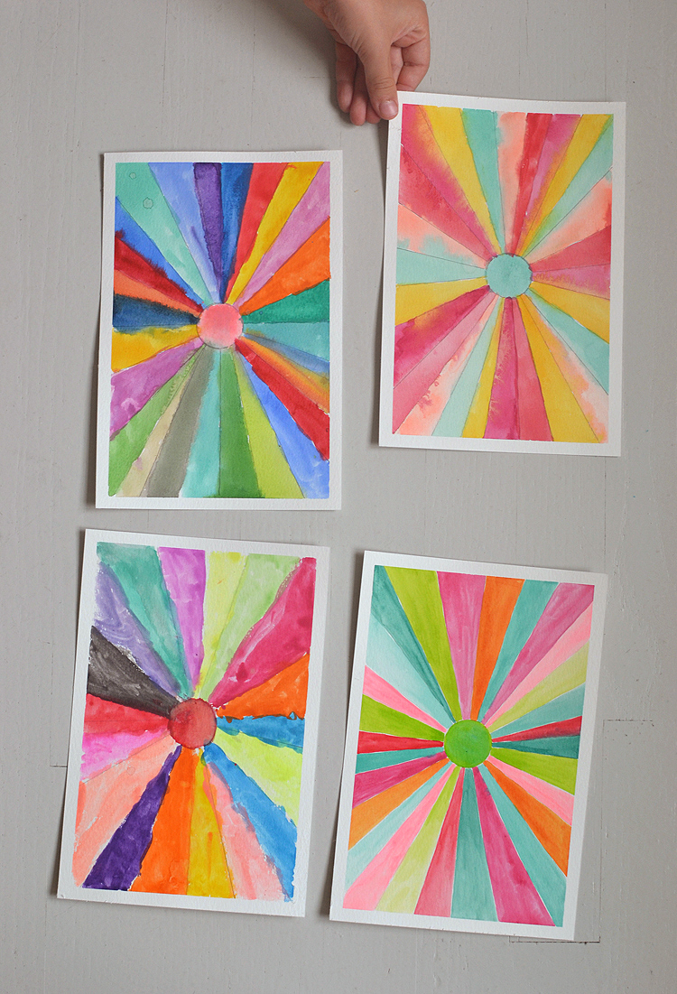 Children draw converging lines then paint them in to make a sunburst.