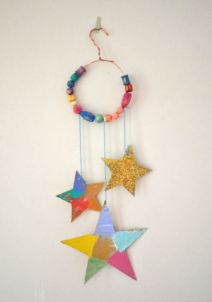 Kids make darling star mobiles using painted wooden beads, cardboard, glitter, and wire.