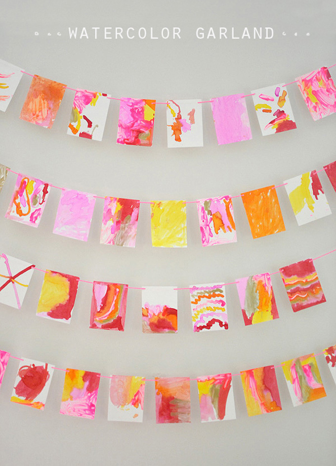 Kids make a garland from small watercolor paintings made with Q-tips and liquid watercolor.