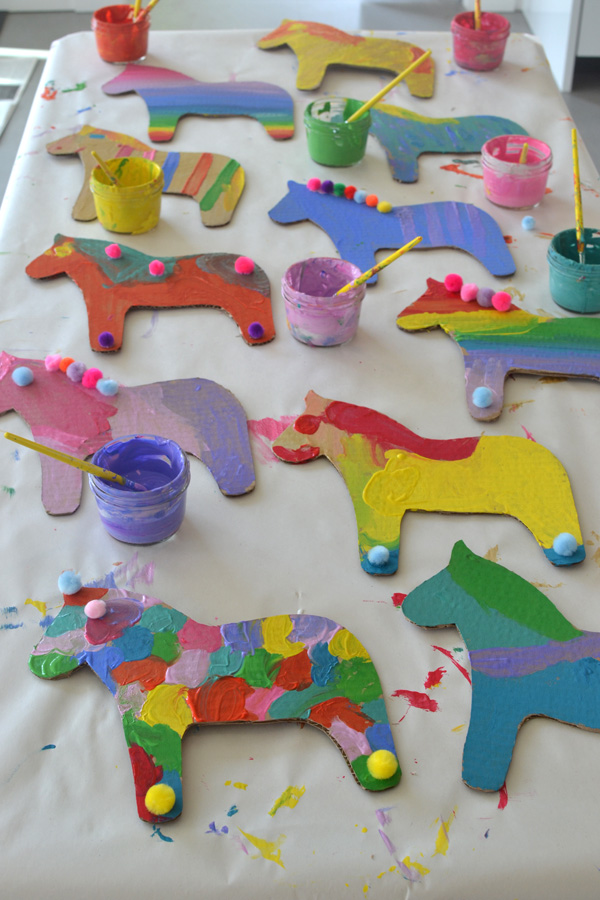 Kids paint cardboard dala horses at a birthday party. Template included.