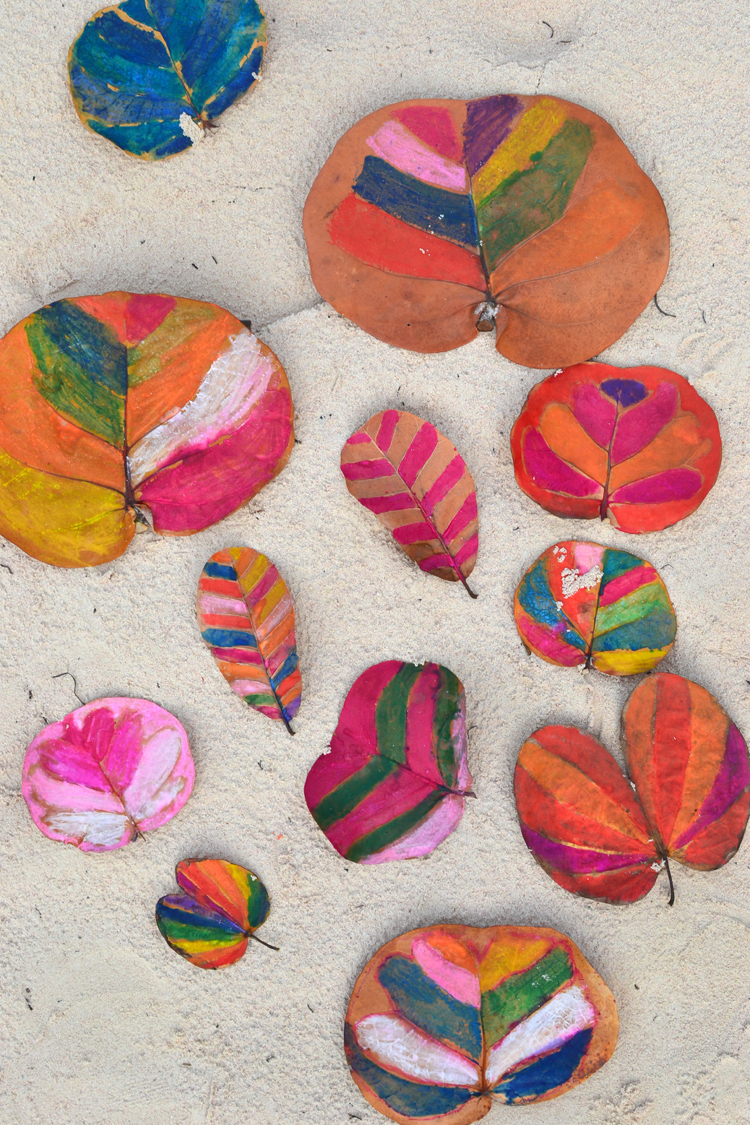 Children and teens paint leaves with water soluble crayons.