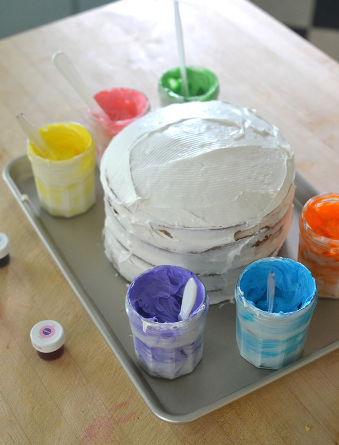 Kids collaborate to paint a cake using colored frosting.