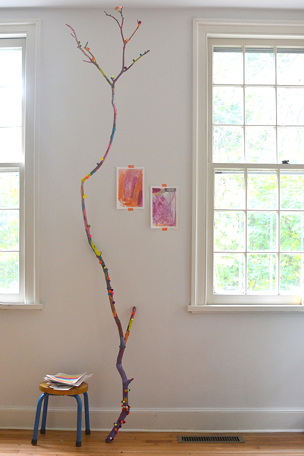 Children collaborate to paint a fallen branch