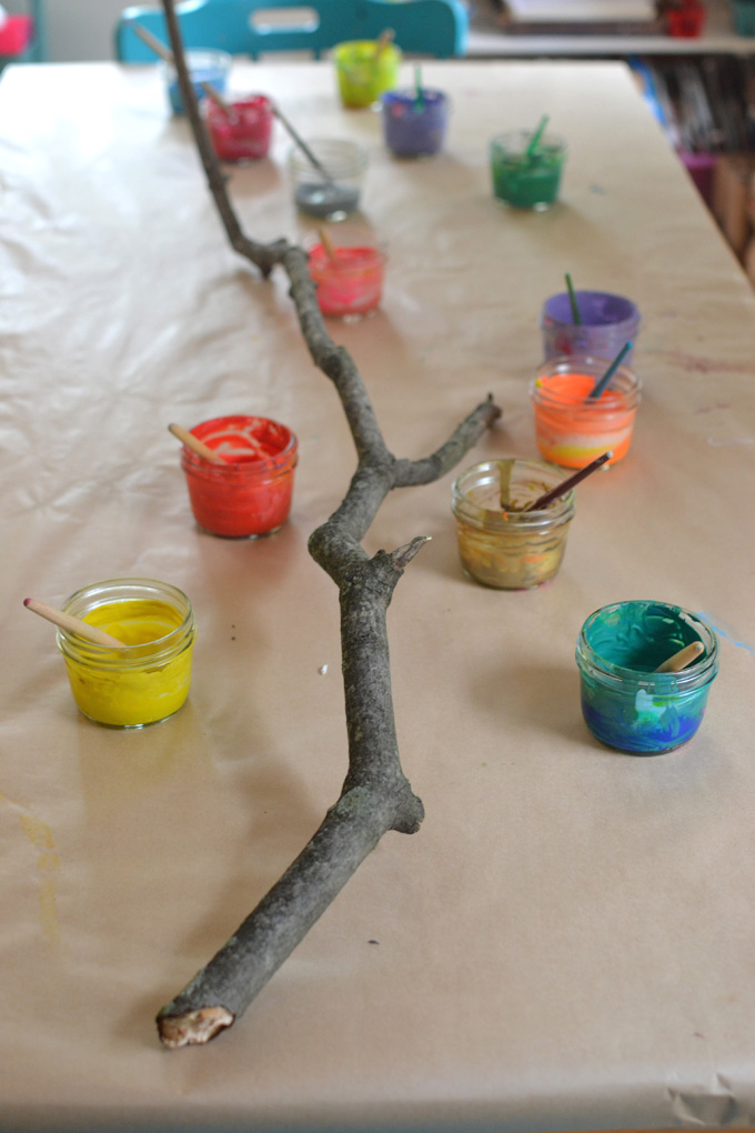 Children collaborate to paint and decorate a large branch. A wonderful process art experience.