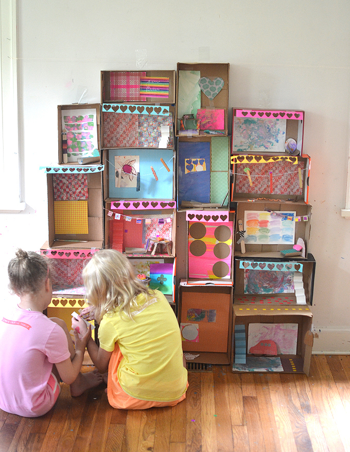 Kids collaborate to make a mansion from shoeboxes, decorating the rooms in the house with handmade furniture from recycled materials.