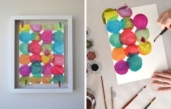 paint circles with liquid watercolor on them - in frame and being painted on tabletop with child's hands