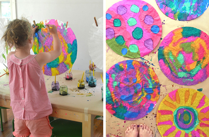 girl painting with liquid watercolor on giant coffee filter and group of painted filters on tabletop