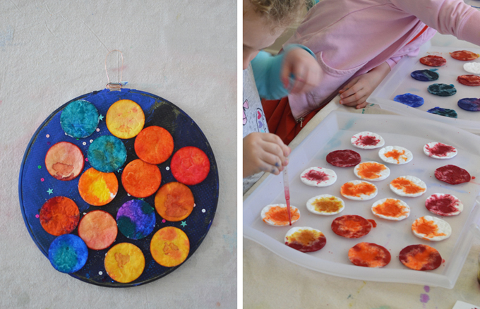 kids use droppers and liquid watercolor to paint cotton rounds and then use as planets in a solar system