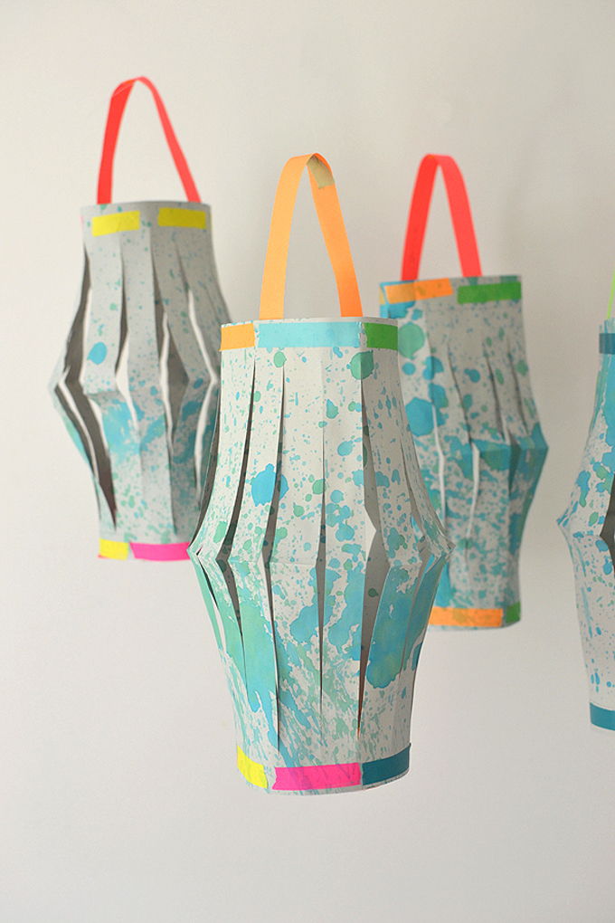 Kids use a splatter paint technique to make the beautiful paper for these lanterns, then they fold, cut, and tape the lanterns all by themselves!