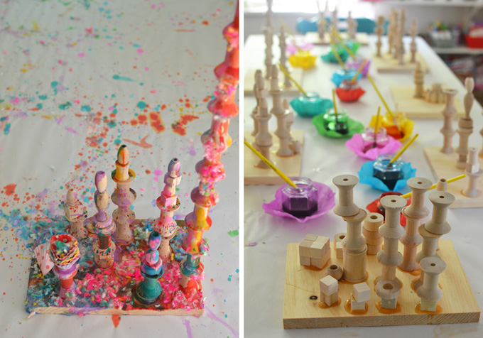 using liquid watercolor to paint wooden towers and then using yarn bits for a mixed-media sculpture
