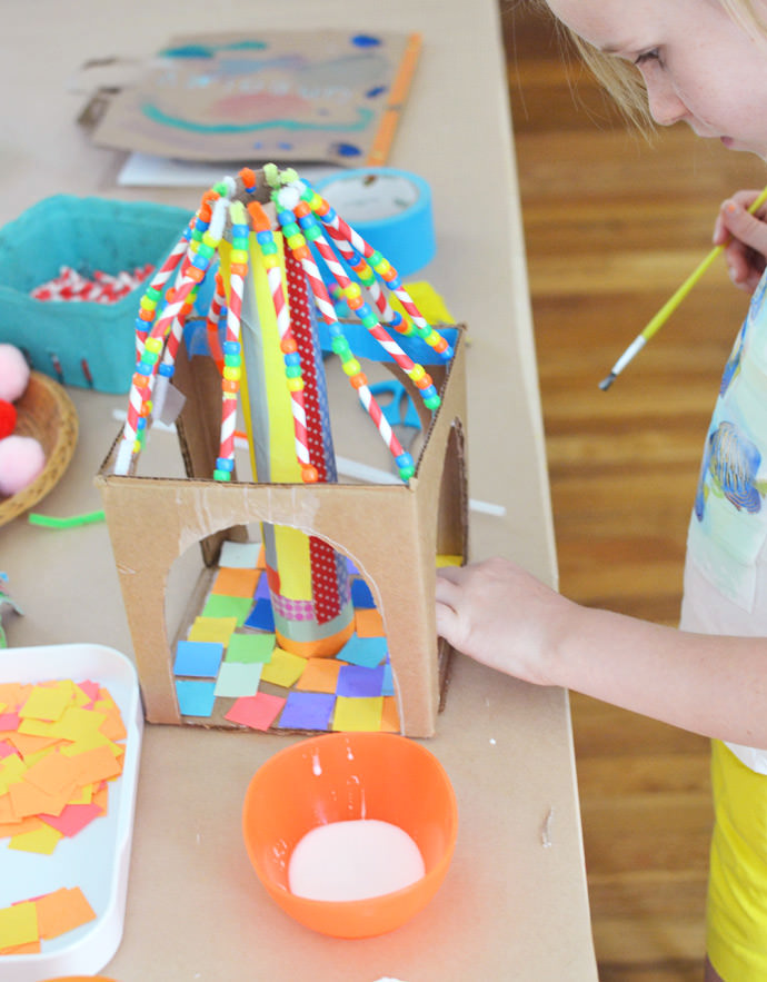 girl gluing little pieces of paper inside a cardboard circus tent