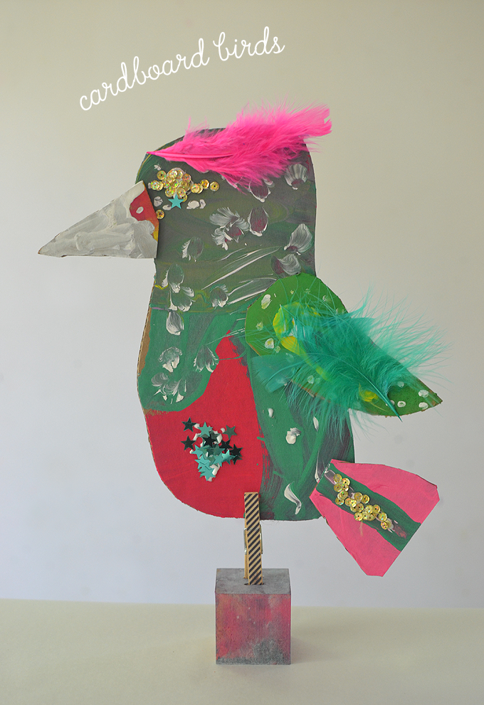 kids make bird sculptures from cardboard, paint, feathers, and a wooden block