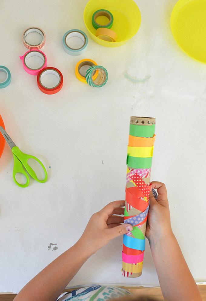 Child wrapping waashi tape around a cardboard tube