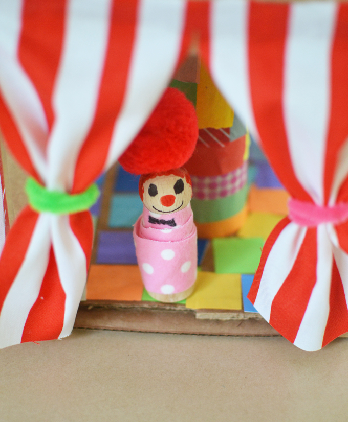 Little decorated peg doll peeking out of circus tent curtains