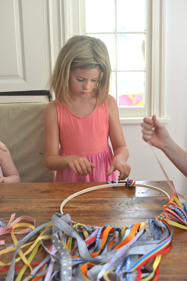 a collaborative chandelier with ribbons and pom-poms made by kids