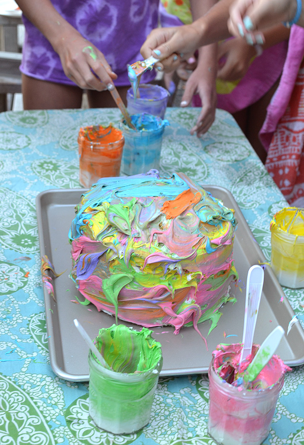 kids collaborate to make an artsy cake with colored frosting