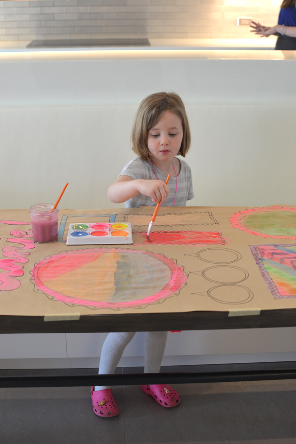Kids collaborate to make a giant painted birthday banner