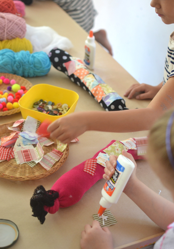 Children make these caterpillars from old socks, fabric pieces, yarn, and pom-poms.