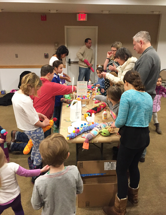 Kids and families make sock caterpillars at a community library event.