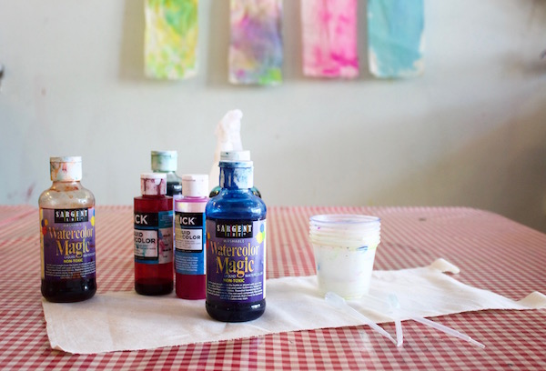 Children use liquid watercolors and spray bottles to design colorful fabric banners.