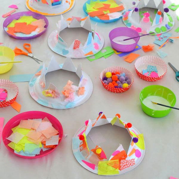 Paper plates are cut into crowns for children to collage into party hats.
