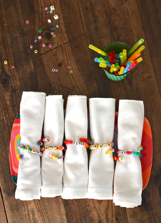 Kids make beaded napkin rings for Thanksgiving with names for each place setting.