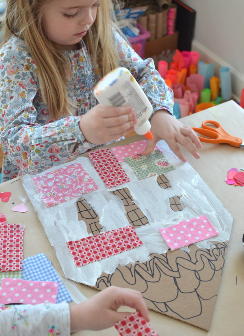 Children make patchwork houses from cardboard and fabric scraps.