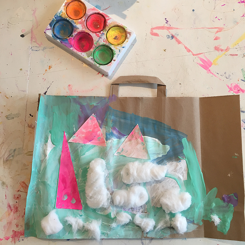 Children create mixed-media collage paintings on recycled paper bags.