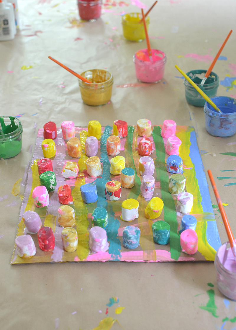 Children collaborate to make a painting from marshmallows