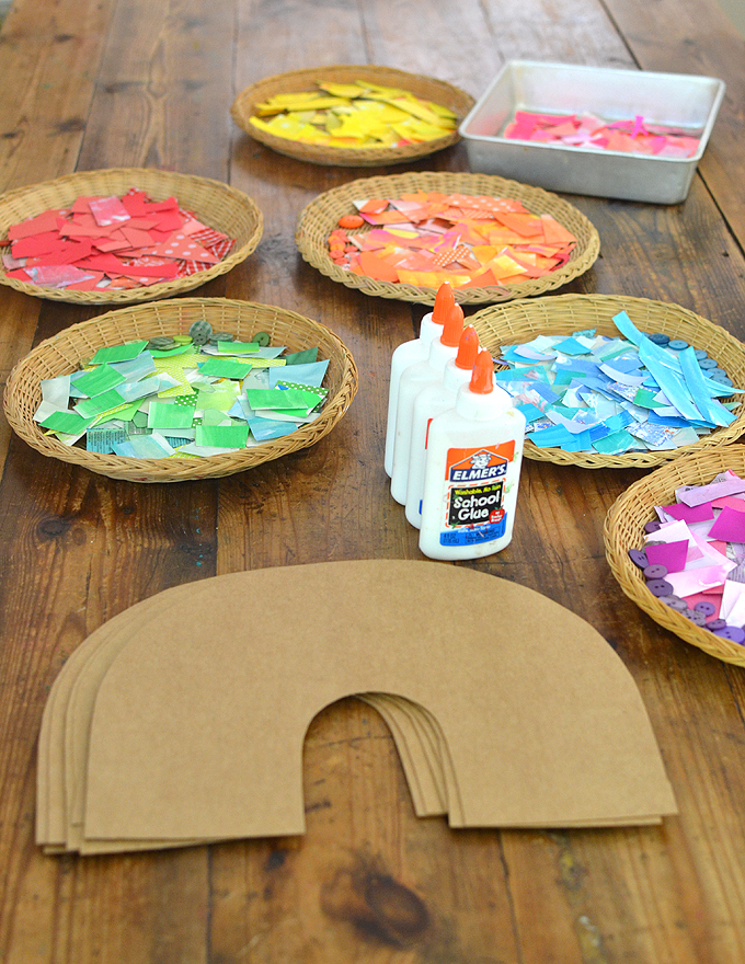 Children use colored collage material to make a rainbow from cardboard.