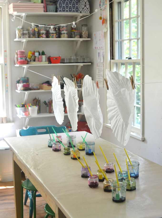Children paint giant coffee filters hanging on a line. A wonderful process art experience.