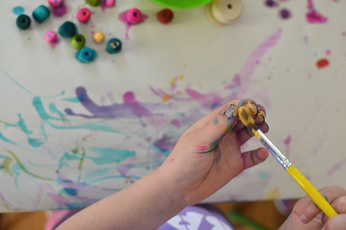 Painting wooden beads for the glitter star mobiles.