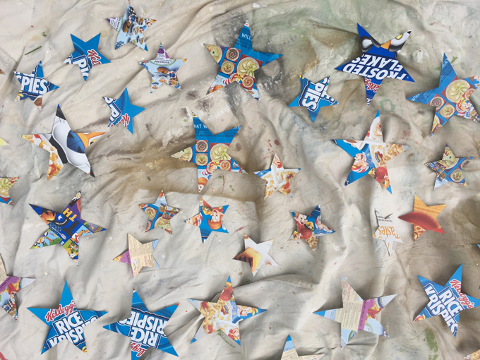 Cereal box cardboard gets cut into stars to make a glittery star mobile.