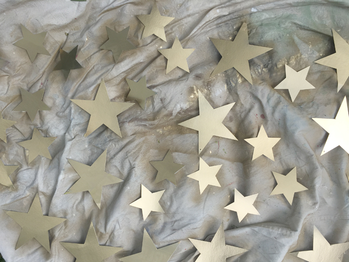 Cereal box cardboard gets cut into stars and spray painted gold to make a glittery star mobile.