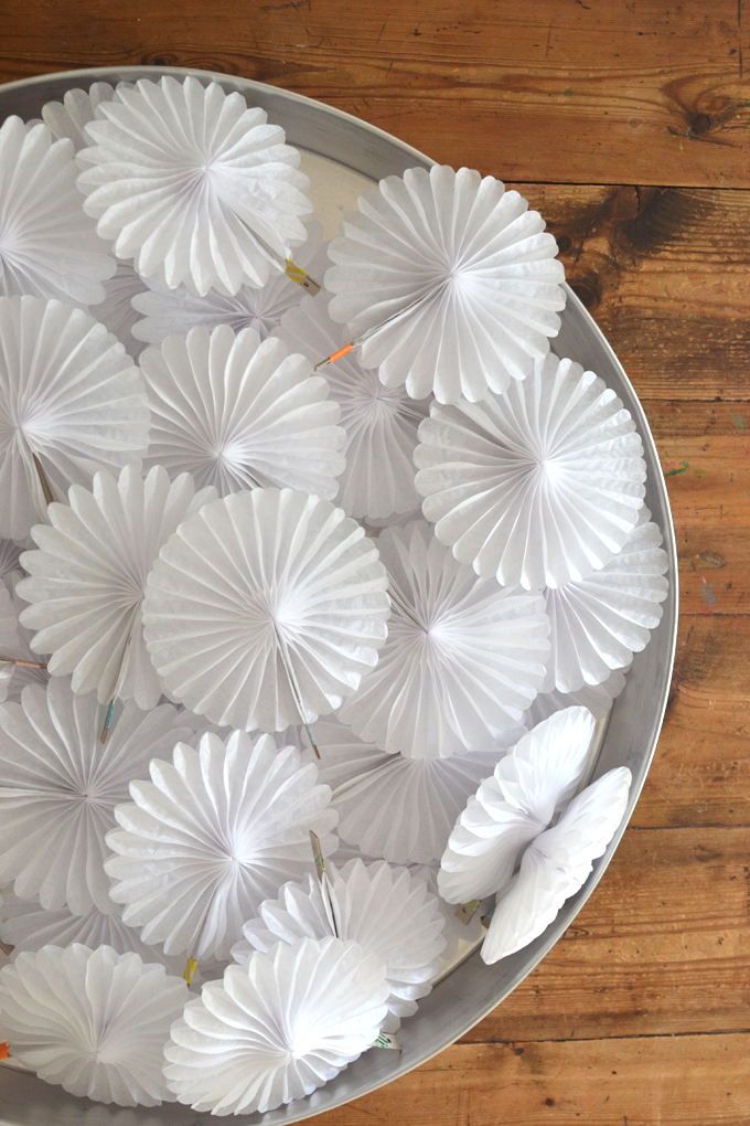 Mini paper pinwheels are set out on a table with paint as a creative invitation.