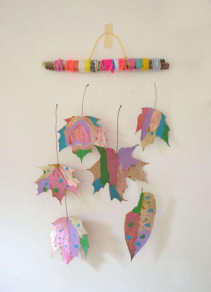 Make a nature mobile with painted leaves and yarn-wrapped twigs.