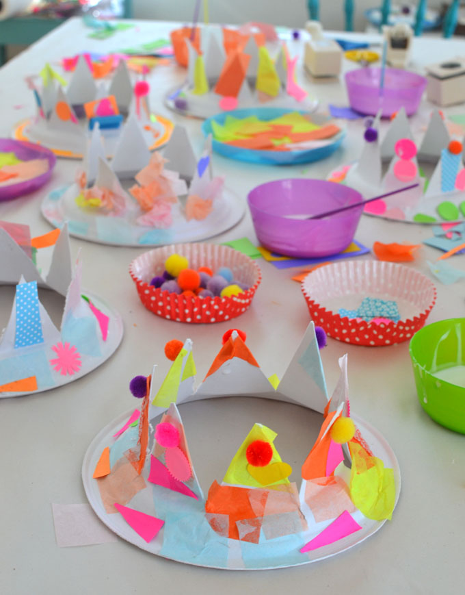 Kids make party hats from paper plates and collage material.