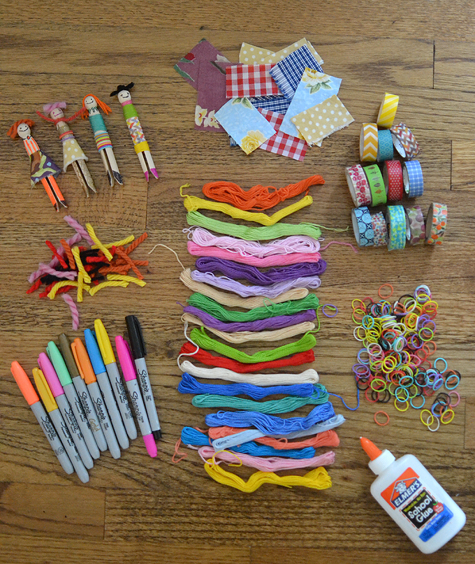 Supplies needed to make wooden peg dolls with fabric scraps and yarn.