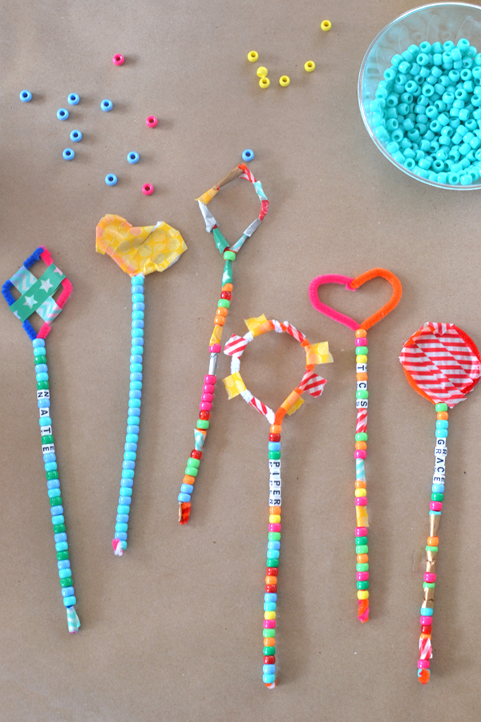 Kids make magic wands from pipe cleaners and beads.