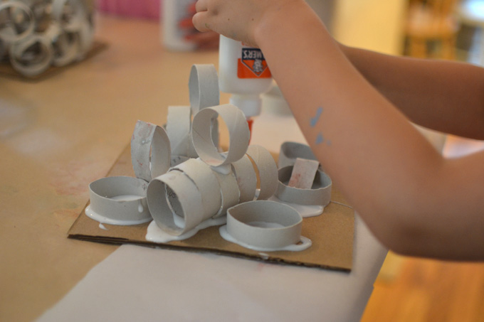 Children use cut up pieces of toilet paper tubes to build sculptures with glue.
