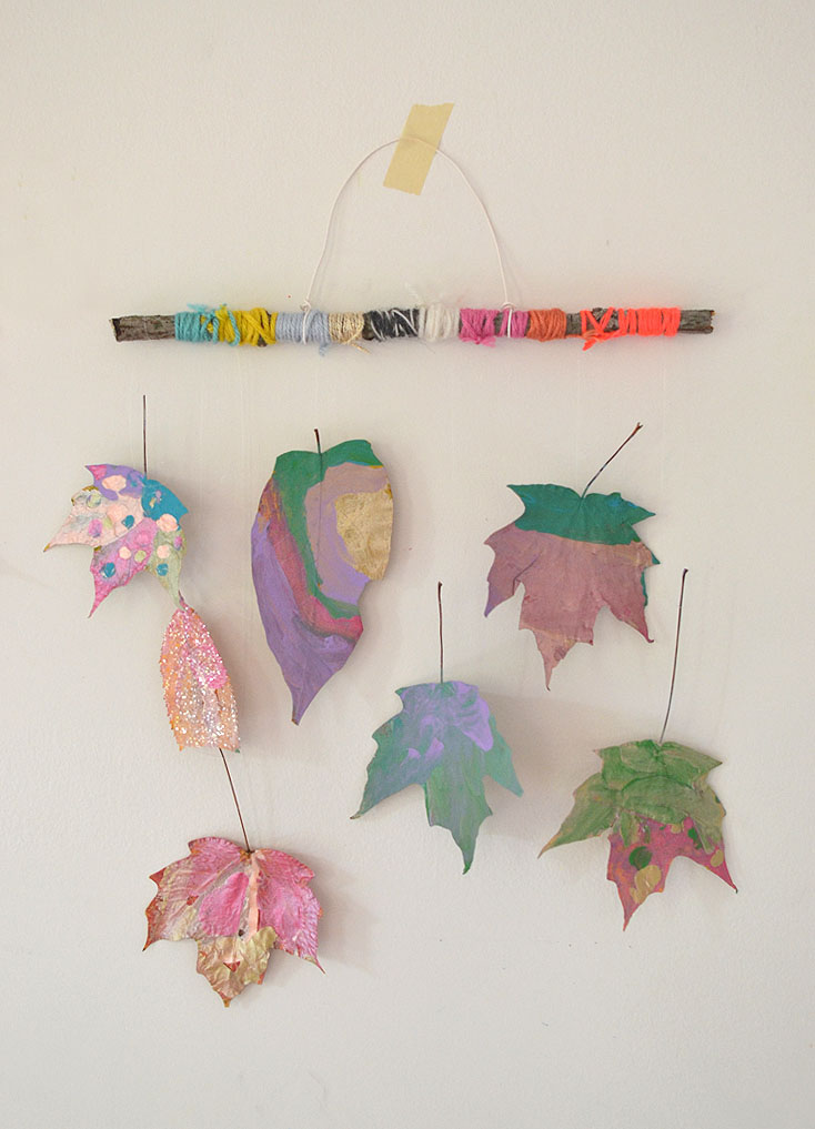 Kids make mobiles from painted leaves and twigs.
