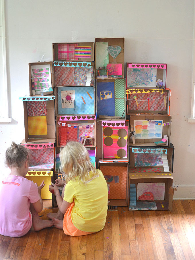 Kids make a structure from shoe boxes.