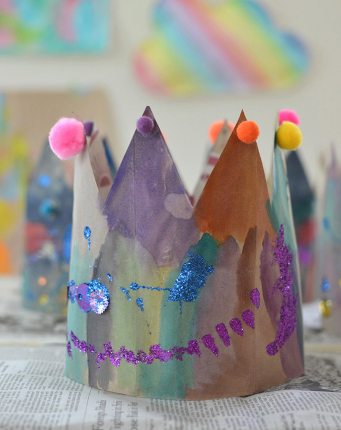 Kids paint and decorate crowns made from paper bags.