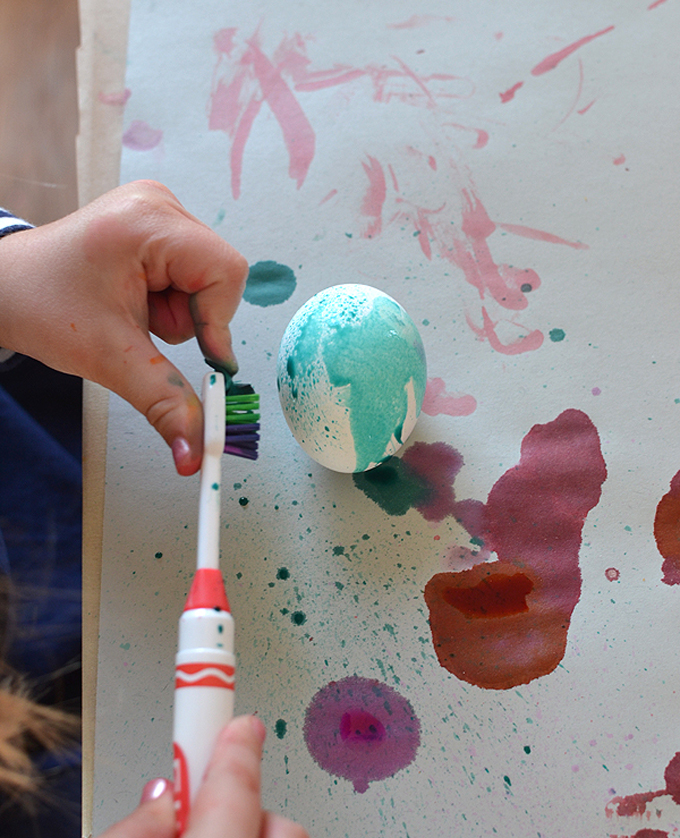 Kids paint eggs with toothbrushes.