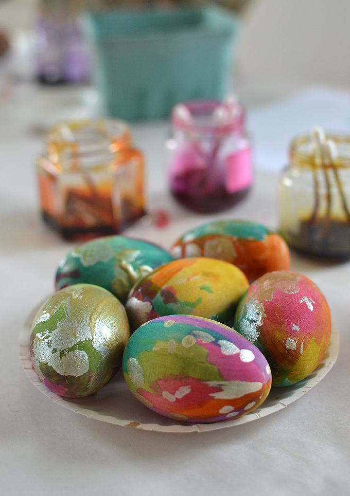 Children paint gorgeous wooden eggs for Easter.
