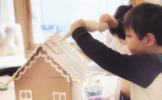 Kids use homemade puffy paint to decorate giant cardboard gingerbread men and cardboard gingerbread houses.