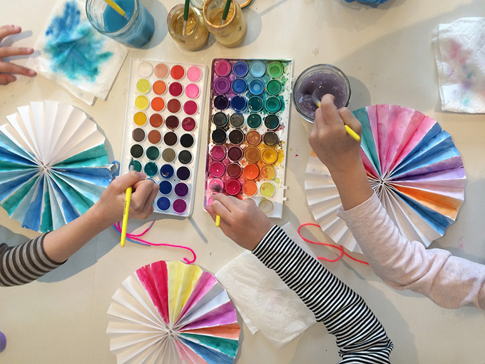 Kids paint homemade paper pinwheels at a birthday party.