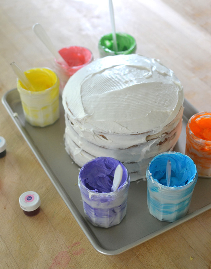 Kids decorate a birthday cake together with a paint palette of different colored frostings.