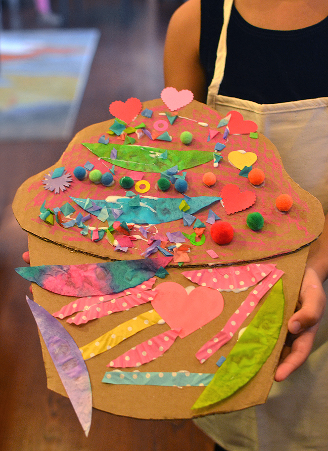 Children make giant cardboard cupcakes with oil pastels and collage, inspired by the artist Wayne Thiebauld.